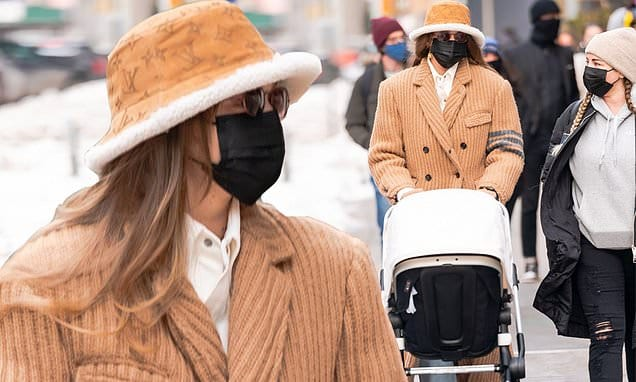 Gigi Hadid models a heavy knit tan trench-style winter coat and matching Louis Vuitton hat in Noho | Daily Mail Online